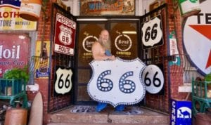 Harley Russell poses for a photo with some of his Route 66 signs in front of the Sandhills Curiosity Shop in Erick in this 2019 photo. [Photo by Jordan Green/The Blackwell Journal-Tribune]